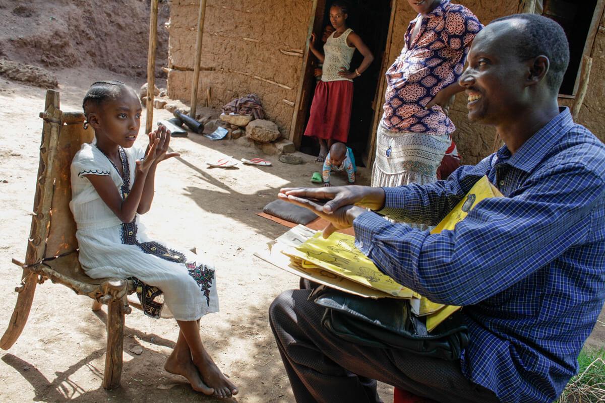 Ein Mann sitzt vor einem Mädchen auf dem Sessel und unterhält sich mit ihr in Gebärdensprache. Sie trägt ein weißes Kleid und schaut ihn konzentriert an, während er mit einem Lächeln erklärt.