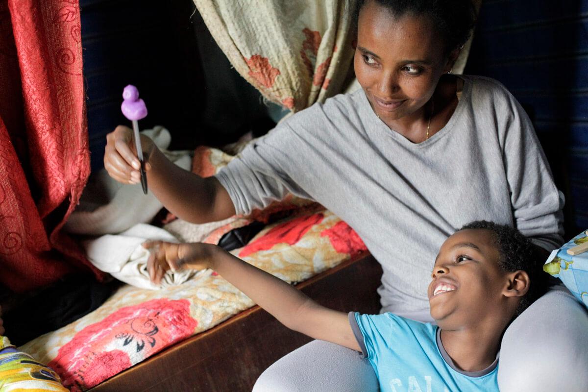 Abdi sitzt im Schoß seiner Mutter. Sie trägt ein graues T-Shirt und eine graue Leggings, er ein blaues Shirt. Der Bub zeigt mit einem Lächeln uaf einen Stift mit einer lila Plastikente, den seine Mutter hochhält.