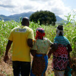 Ein Licht für die Welt Mitarbeiter begleitet zwei Frauen auf dem Weg durch ein gründes Feld.