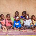 Viele Kinder mit und ohne Behinderungen sitzten vor einer braunen Wand. Sie sind alle bunt angezogen und lachen.