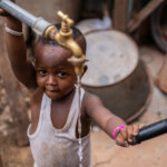 Small child looking at the camera while holding a water tank where water is coming out.