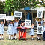 10 indian children outside holding advocacy signs for inclusion. Amongst them is a child sitting on a red rollable chair.