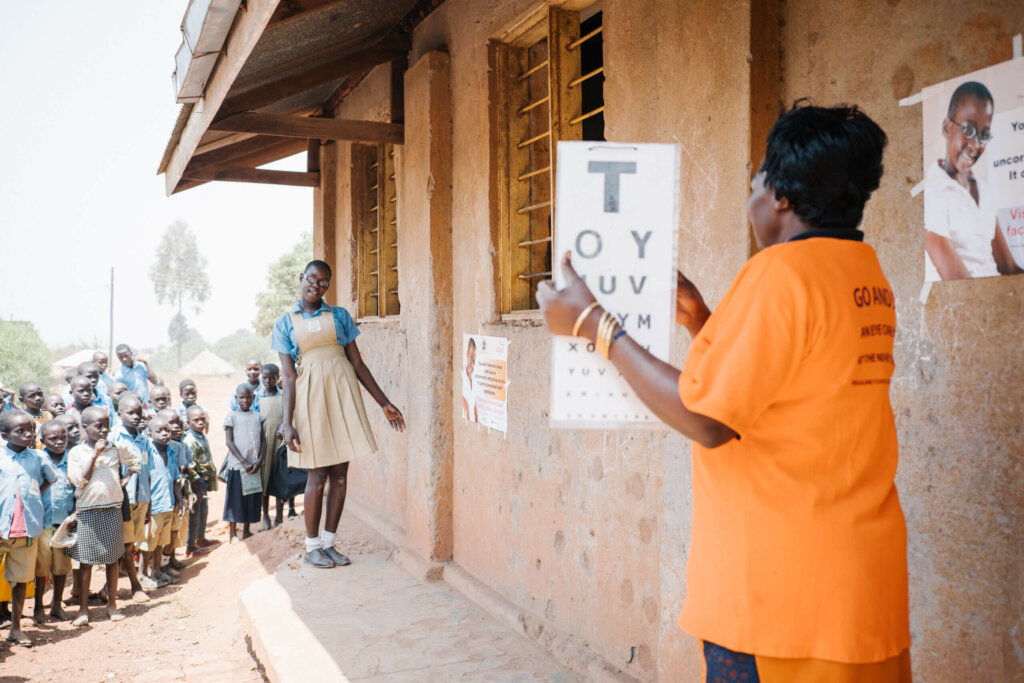 A eye health worker is holding up a vision screen test with letters. A girl student wearing glasses and the school uniform is a couple of meters in front of her leaning slightly to the right side with her head, trying to read the letters. Her school peers are behind her watching.