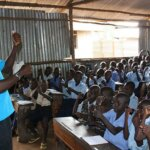 A southsudanese man stands in front of a class full of children talking to them in sign language.