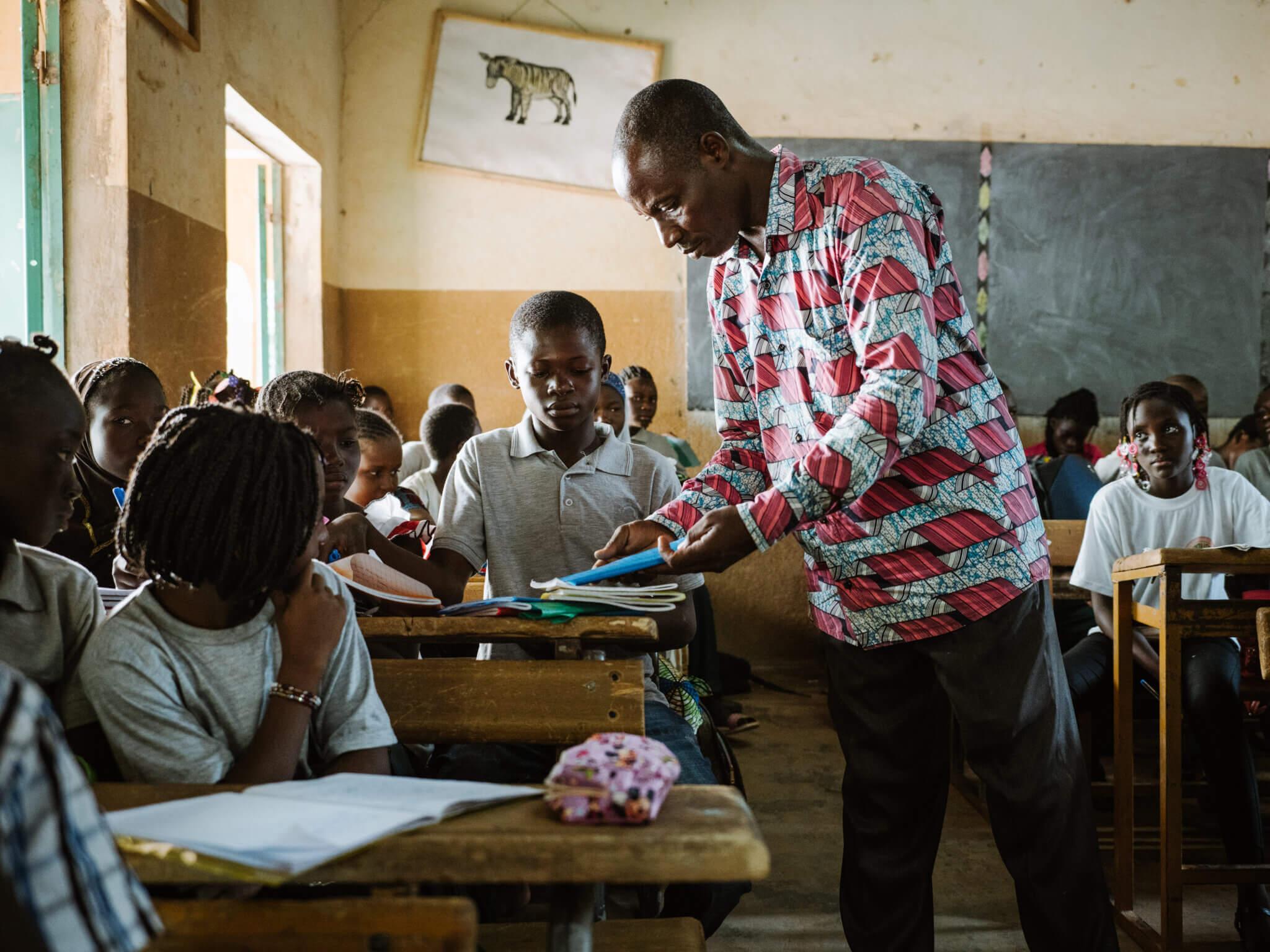 Ein Lehrer in einem bunten Hemd gibt einem Jungen sein Heft im Klassenzimmer zurück.