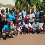 Eine große Gruppe von Menschen aus dem Südsudan steht in einer Gruppe vor der Kamera und freut sich über die Entwicklung des ersten Wörterbuchs für Gebärdensprache