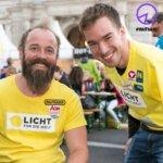Thomas Geierspichler und Andi Onea lachen mit einem Licht für die Welt T-Shirt in die Kamera.