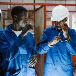 Zwei junge Männer in blauen Overalls unterhalten sich mit Gebärdensprache. Einer von ihnen trägt einen weißen Helm.
